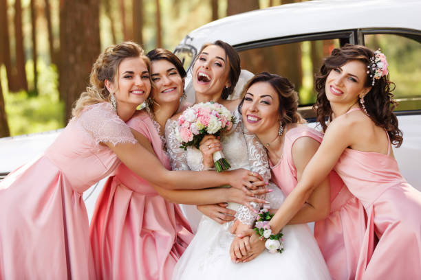 Wedding photography of happy bride and bridesmaids in pink dresses embracing with smile on wedding day stock photo
