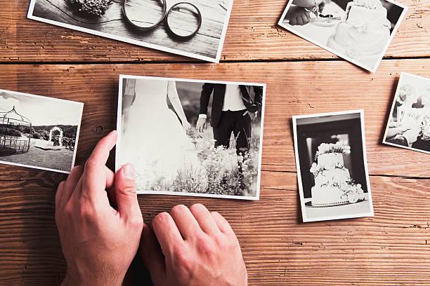 hochzeitsfotos auf einem tisch - bräutigam anzug vintage stock-fotos und bilder