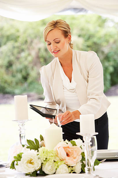 Wedding Planner Checking Table Decorations In Marquee stock photo