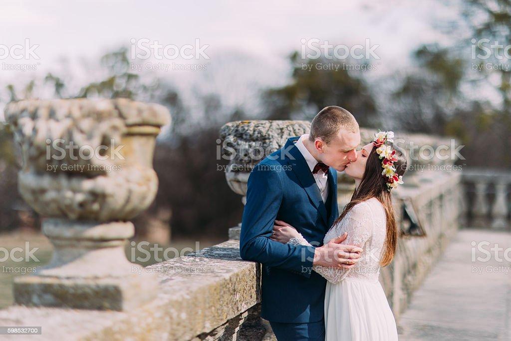 Wedding portrait of stylish newlywed couple passionately kissing at old photo libre de droits