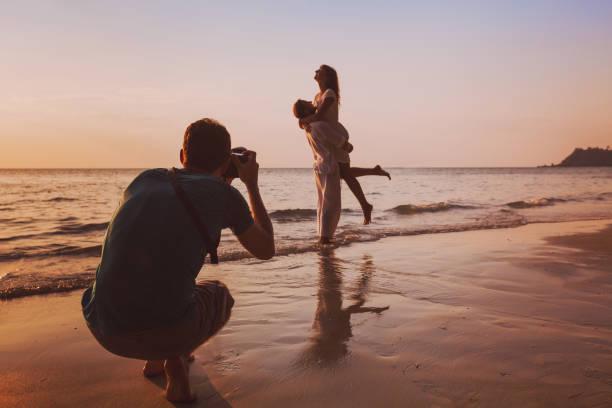 wedding portrait photographer taking photos of honeymoon couple on the beach stock photo