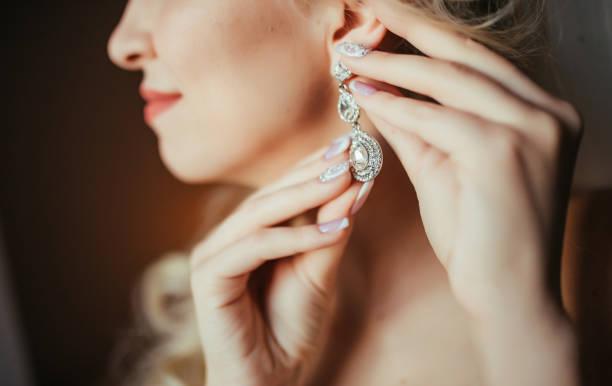 Wedding preparation. Beautiful, happy bride dresses earrings before wedding. Wedding accessories, jewelry. Closeup portrait of bride. Selective focus. stock photo