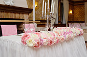 Wedding presidium in restaurant, copy space. Banquet table for newlyweds with pink and beige flowers. Lush floral arrangement. Luxury wedding decorations