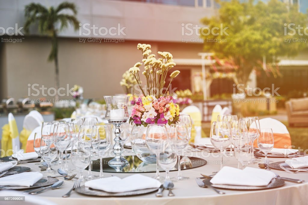 Wedding Reception Dinner Table Arrangement With Flower Decoration And White  Chairs Royalty Free Stock Photo