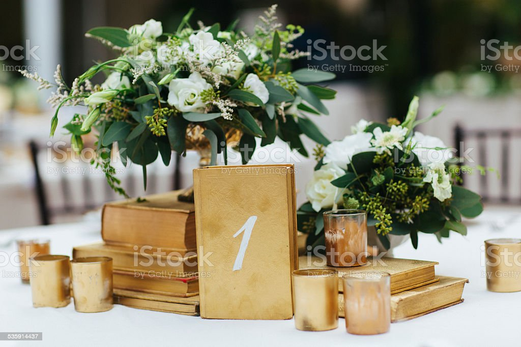 Wedding Reception Table Decor with Gold Accents and Flower Arrangements stock photo