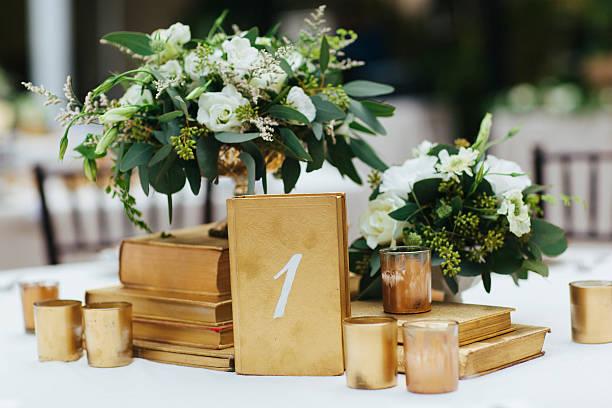 tisch für hochzeitsempfang dekor mit goldenen akzenten und blumenarrangements - grüne hochzeit themen stock-fotos und bilder