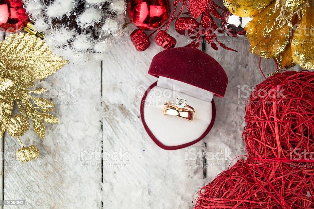 Wedding ring among Christmas decorations on wood background. stock photo
