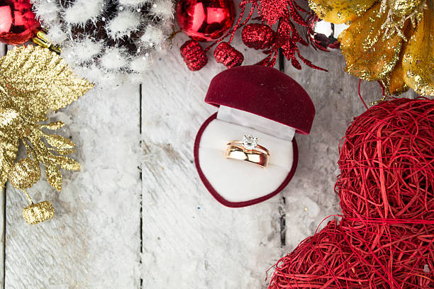 Wedding ring among Christmas decorations on wood background. stock photo