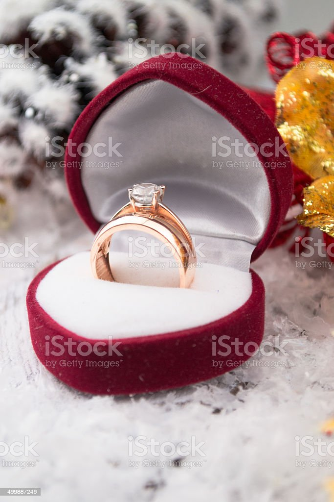 Wedding ring among Christmas decorations on wood stock photo