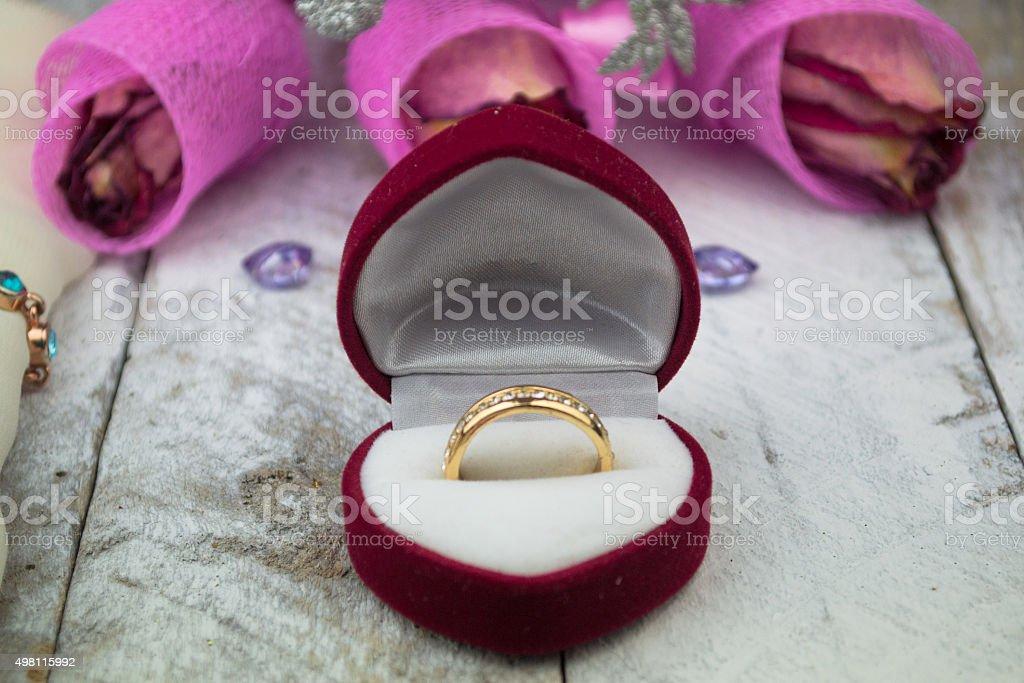 Wedding ring among roses on wood background stock photo