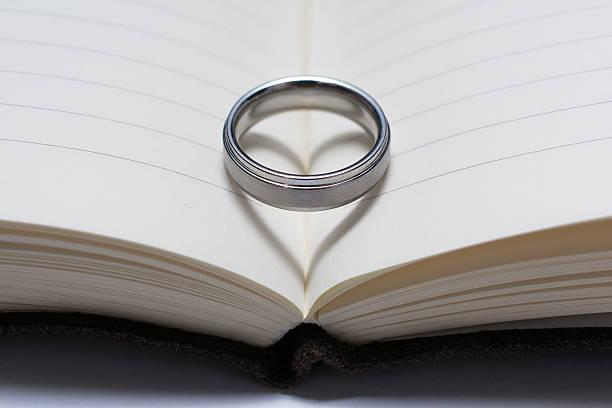 wedding ring band on book spine with heart shadow - verse zur hochzeit stock-fotos und bilder