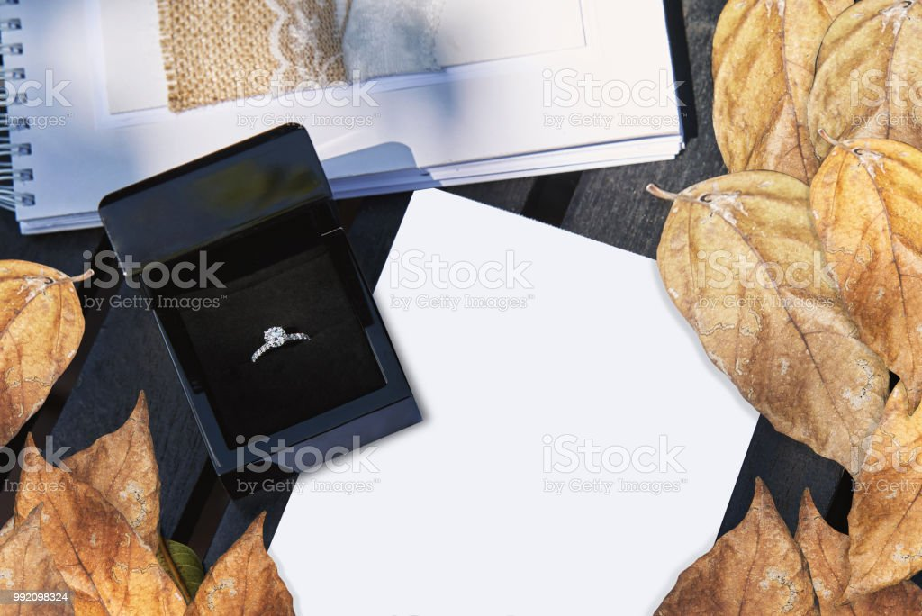 Wedding ring in black box on white blank paper with dry leafs decoration stock photo