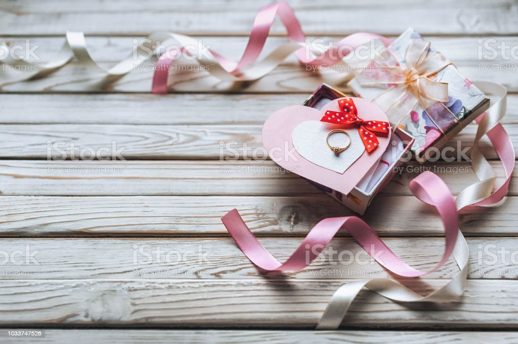 A wedding ring on a gift box with ribbons and hearts on a grey wooden...
