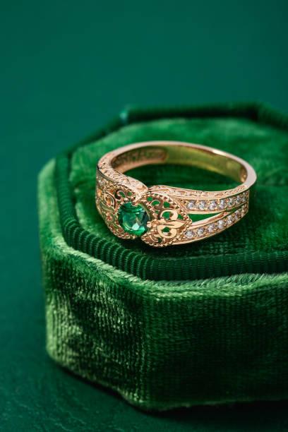 Wedding ring with emerald green gemstone on green velvet jewelry box