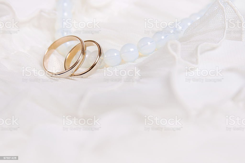 Wedding rings and blue beads royalty-free stock photo
