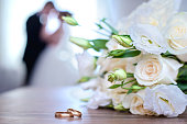 Gold wedding rings and bouquet from white roses on a background of blurred newlyweds
