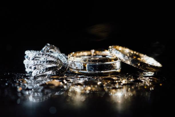 hochzeit ringe und ohrringe sind nass, mit tropfen. spiegelungen auf dem glas sind professionell - ohrringe tropfen stock-fotos und bilder