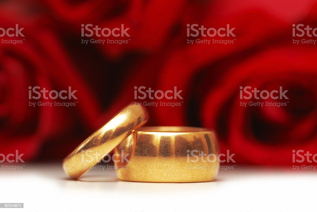Wedding rings and roses at the background royalty-free stock photo