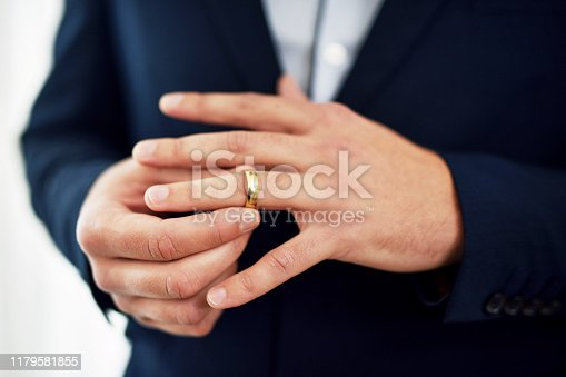 Cropped shot of an unrecognizable bridegroom adjusting his ring on his wedding day