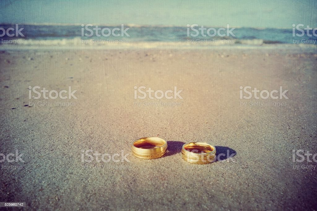 Wedding rings at the beach with copy space stock photo