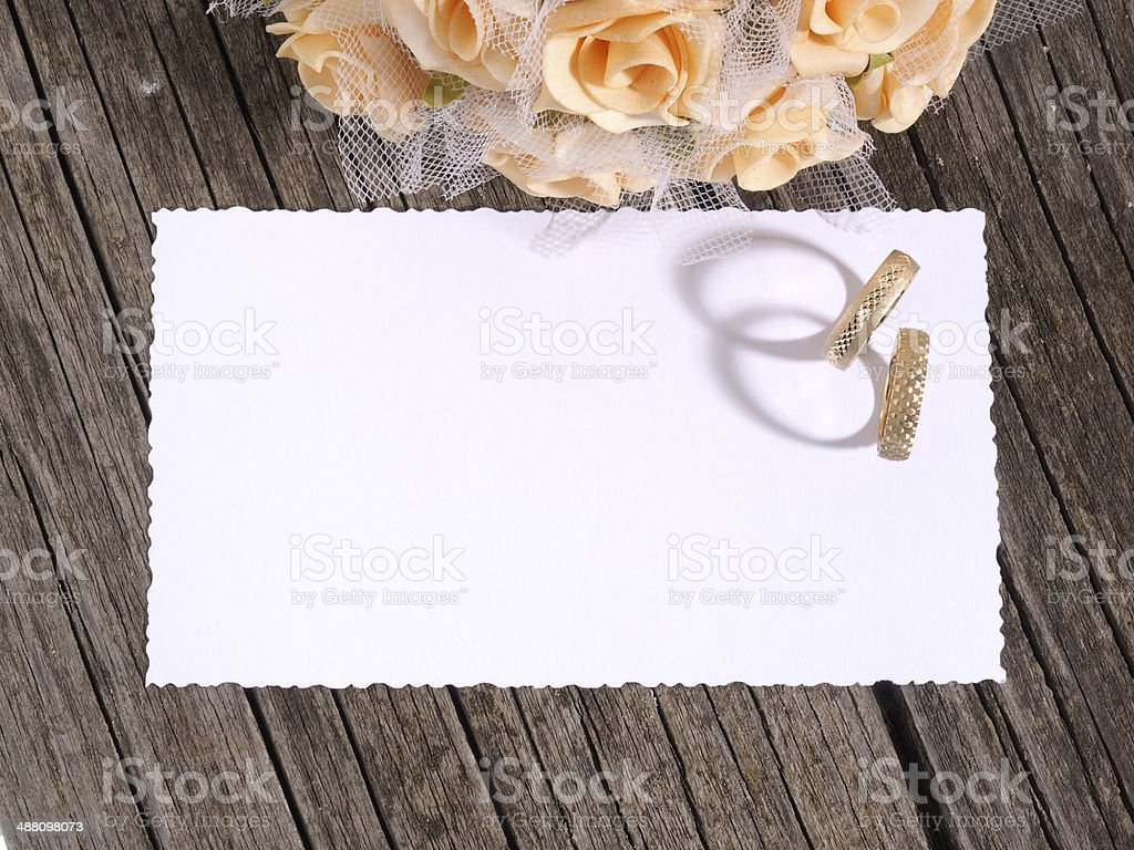 Wedding rings, card and flowers stock photo