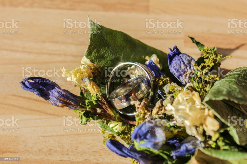Wedding rings in dry flower on wooden background stock photo