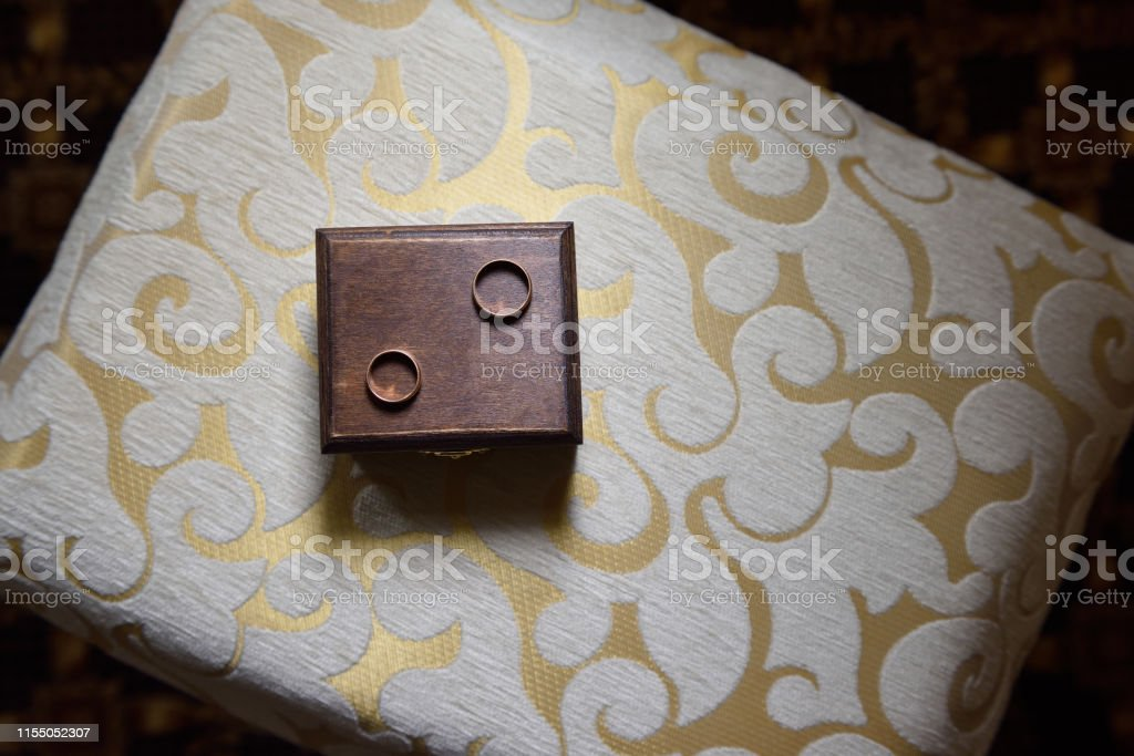 Wedding rings lie on a wooden box. Wedding rings and box in rustic...