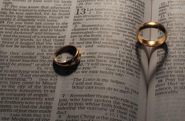 hochzeitsringe, herzförmigen schatten auf bibel-seiten - verse zur hochzeit stock-fotos und bilder