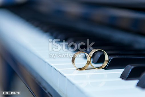 istock wedding rings of piano and black and white background. 1130680276