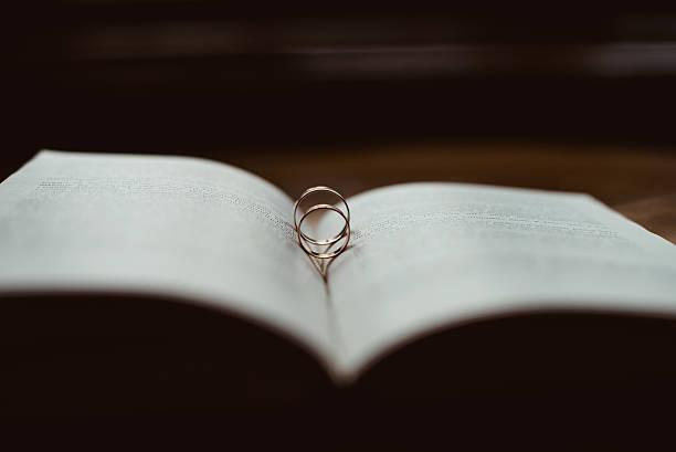 wedding rings on a bible - verse zur hochzeit stock-fotos und bilder