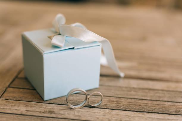 wedding rings on a light wooden texture in a blue box. wedding j - hochzeitsbox stock-fotos und bilder