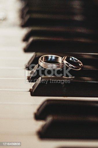 Two wedding rings on piano keys.