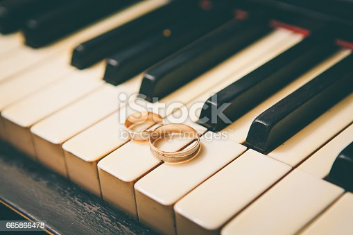 istock wedding rings on a piano 665866478