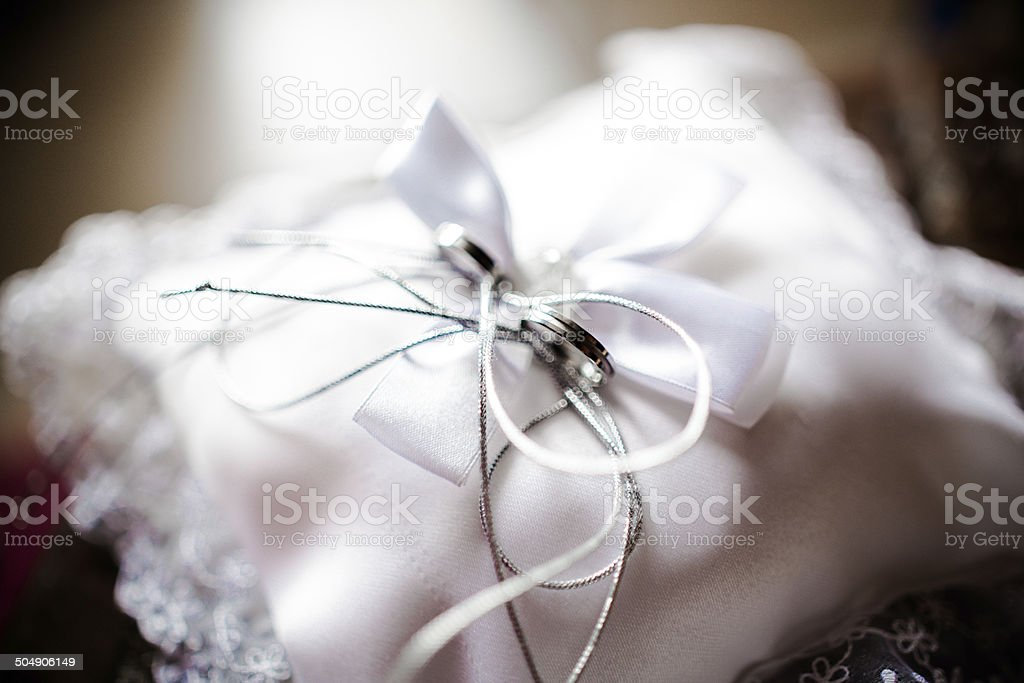 Wedding rings on a pincusion with a bow stock photo