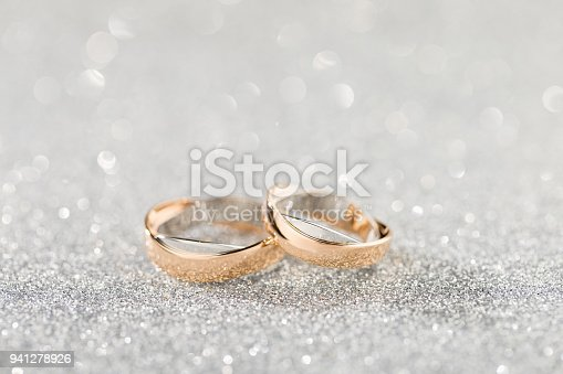 istock Wedding rings on a silver sparkling glitter background with bokeh 941278926