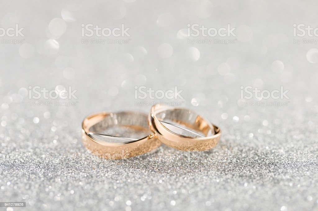 Wedding rings on a silver sparkling glitter background with bokeh stock photo