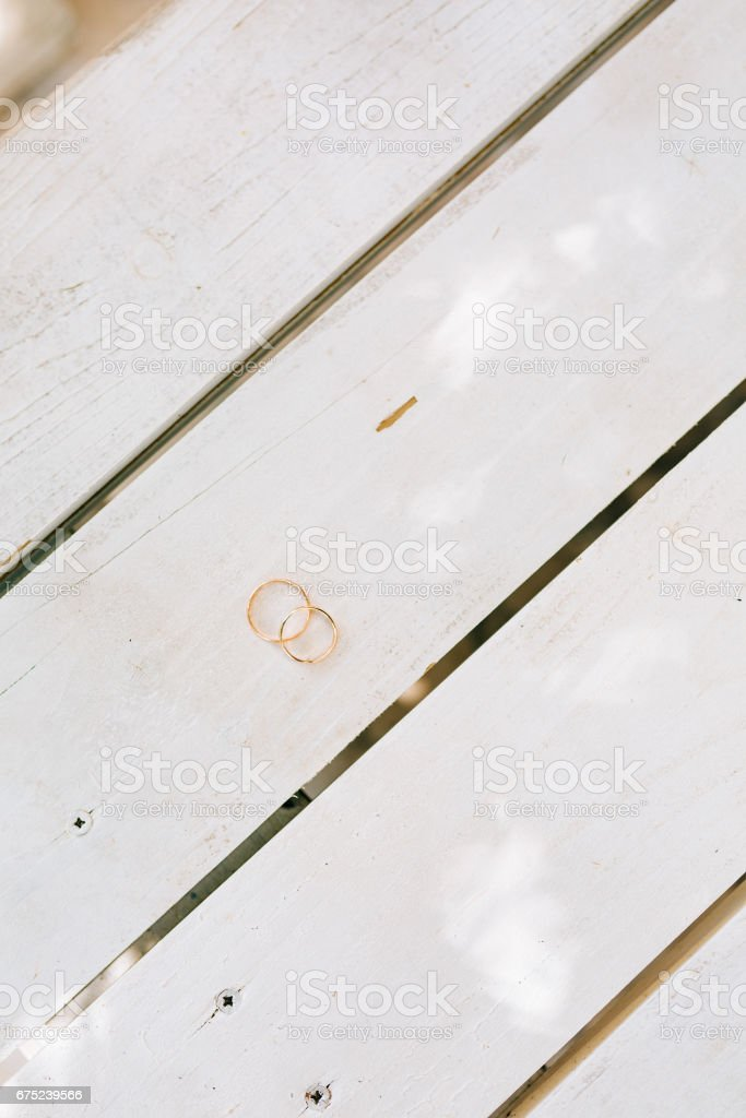 Wedding rings on a white wooden texture royalty-free stock photo