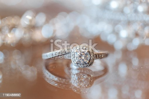 Wedding rings with diamonds on bride's bouquet made with white poppies, dahlias and gemstones