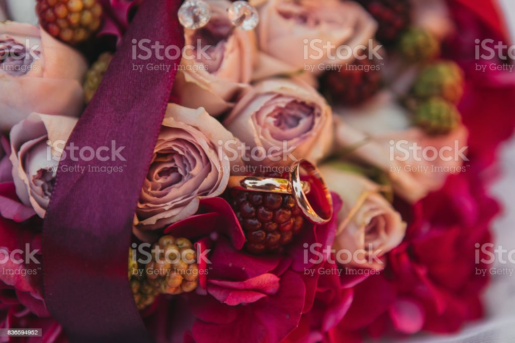 wedding rings on colorful flowers stock photo