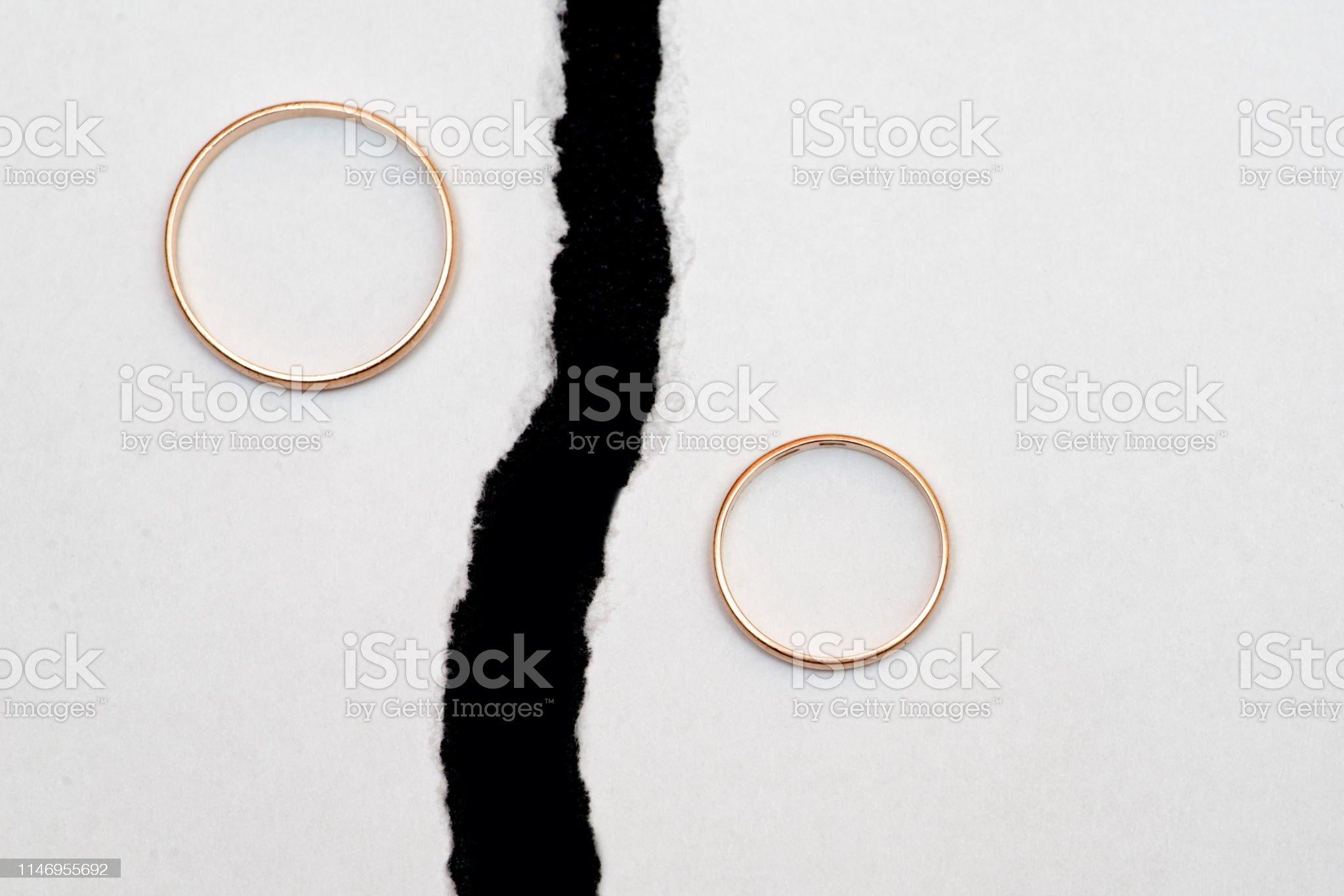 Anéis de casamento em metades diferentes de uma folha rasgada do livro branco. - Foto de stock de Aliança de noivado royalty-free