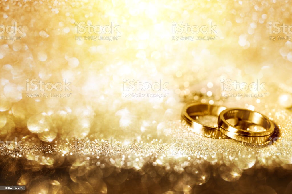 Wedding rings on festive golden background stock photo