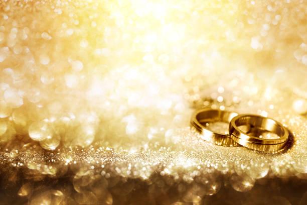 trauringe auf festliche goldgrund - verlobungsfeier einladungen stock-fotos und bilder