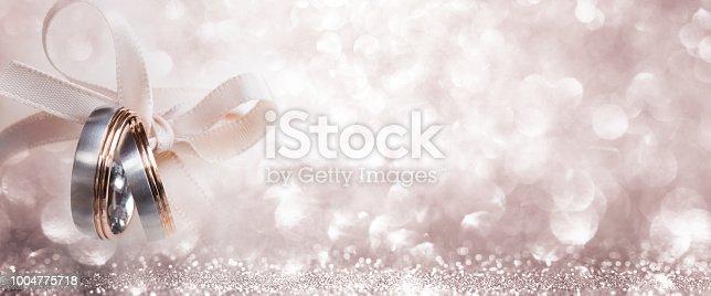 155315629istockphoto Wedding rings on festive silver background 1004775718