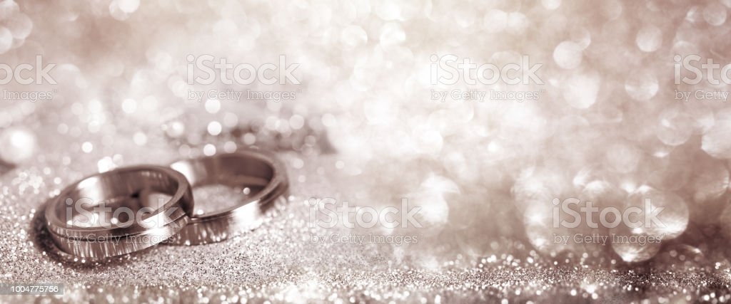 Wedding rings on festive silver background stock photo