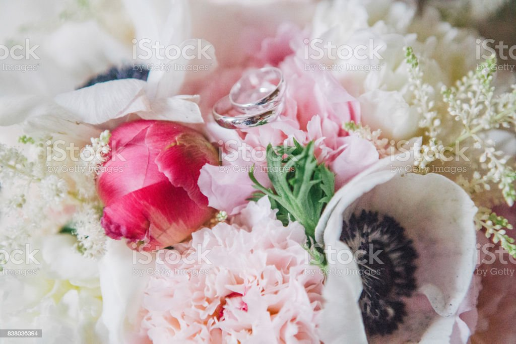 wedding rings on flowers stock photo