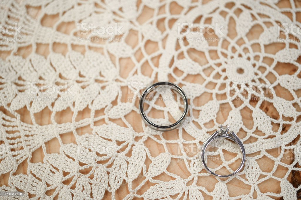 Wedding rings on lace doily stock photo