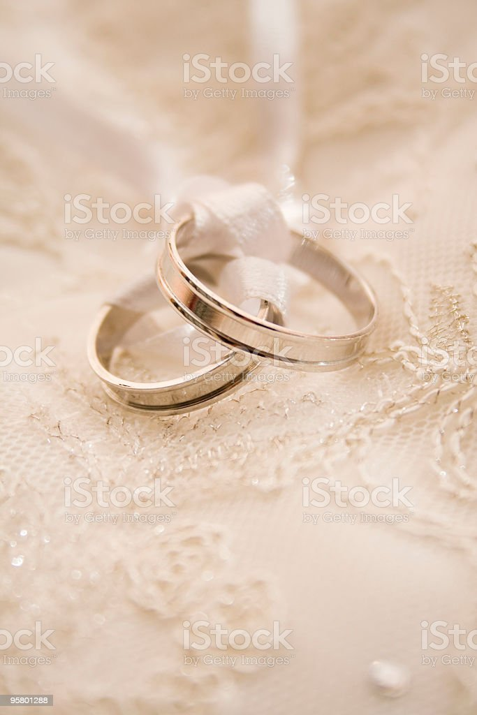 wedding rings on pillow laced with tape stock photo