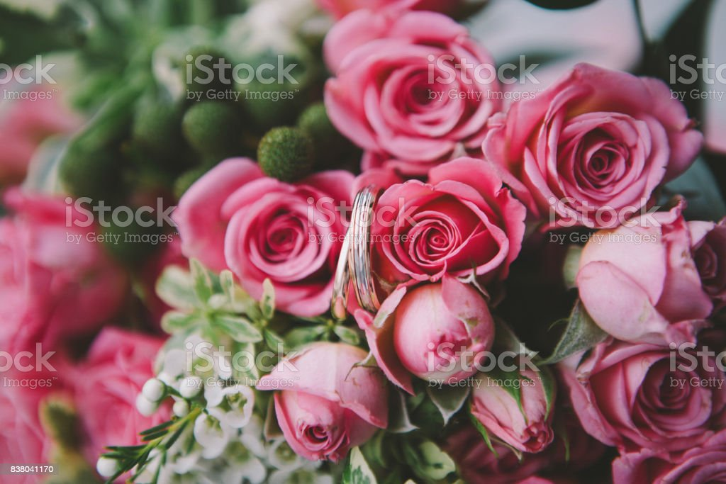 wedding rings on pink flowers stock photo