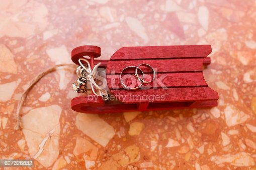 istock Wedding rings on red sleigh, Christmas decoration 627326832