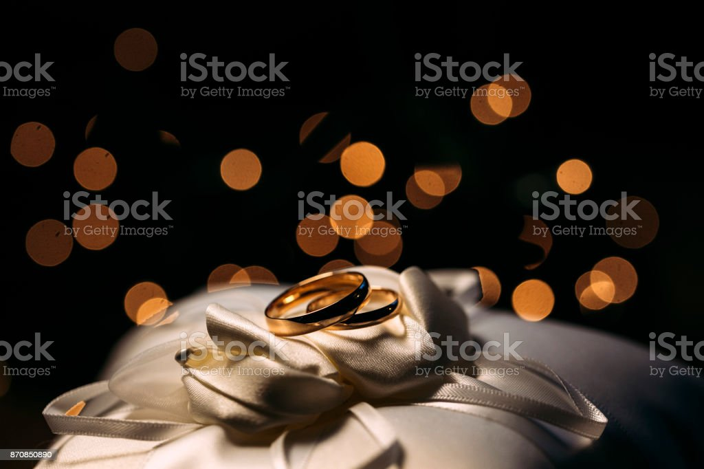 Wedding Rings On Silk Cloth And Bokeh In Background Stock Photo